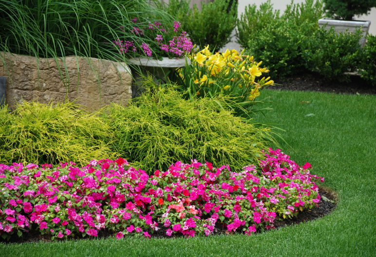 Yard landscaped with artificial grass and flowers