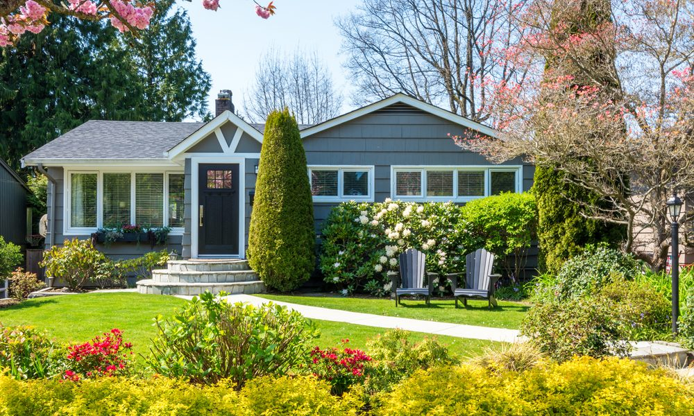 Cozy home exterior with a beautiful lawn and landscaping.