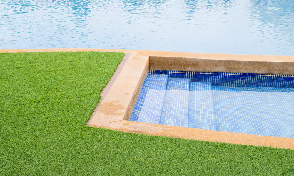 Backyard pool and jacuzzi with artificial grass.