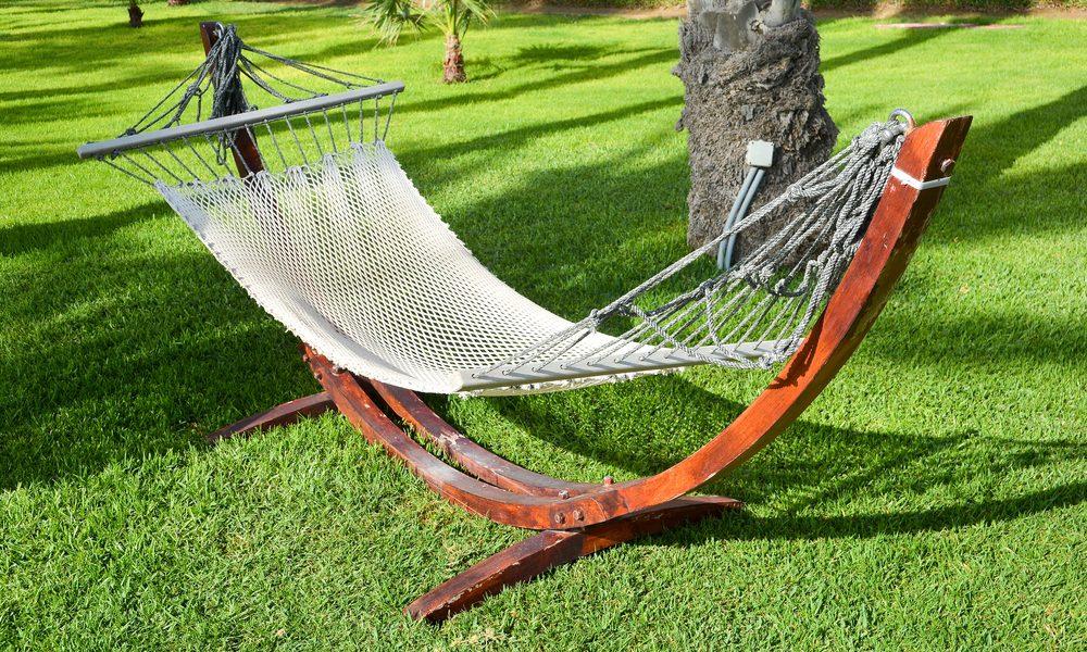 A hammock sits atop an artificial grass backyard