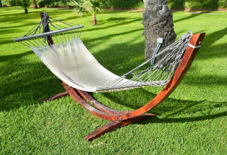 A hammock sits atop an artificial grass backyard