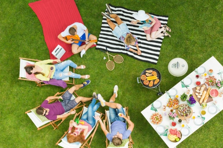People gathered on artificial grass in lawn chairs and on blankets eating and playing games.