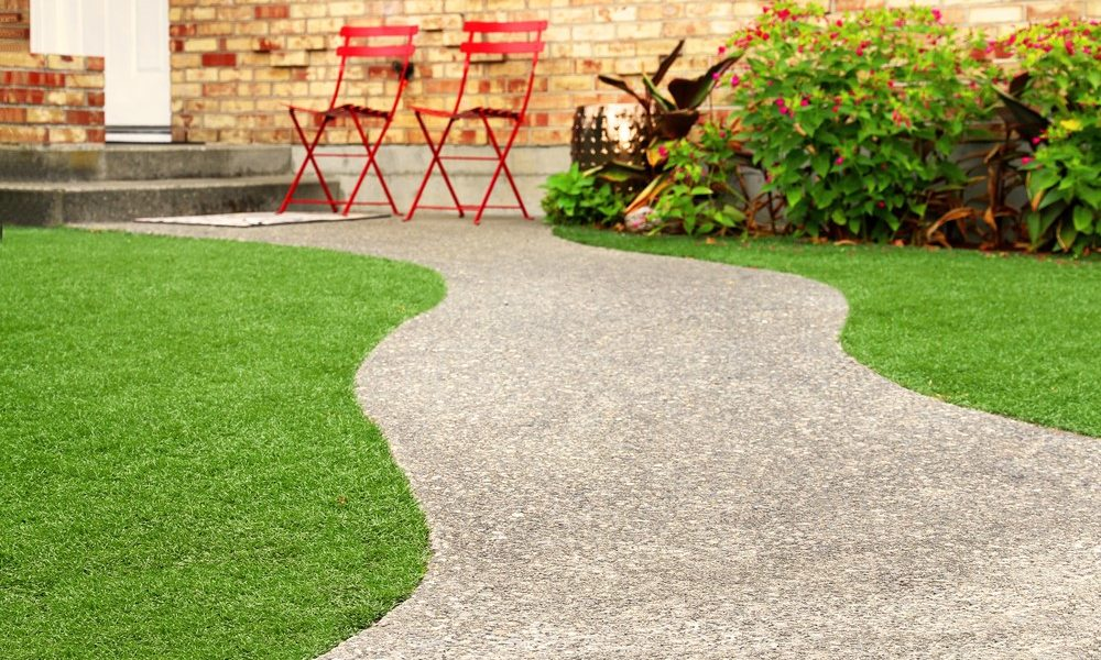 A walkway leading up to a house surrounded by artificial grass.